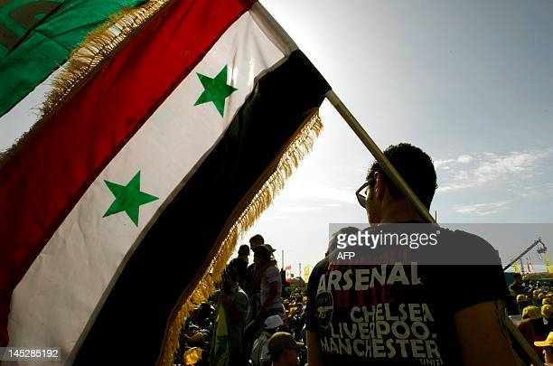 A Lebanese man in an Arsenal Tshirt holds up a Syrian flag during a Hezbollah rally in the southern town of Bint Jbeil on May 25 2012 to mark the...