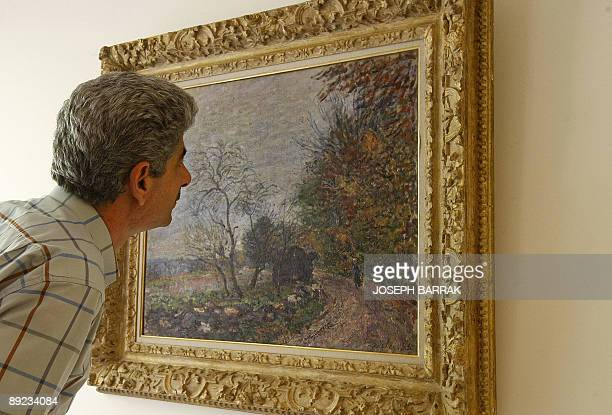 A Lebanese man inspects a 1000 USD Sisley Alfred oil painting displayed at Opera Gallery in downtown Beirut on July 24 2009 The Dubaibased Gallery...