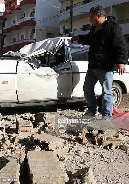 A Lebanese man look at his vehicle damaged by falling debris following an earth tremor in the southern Lebanese city of Tyre on February 15 2008 An...