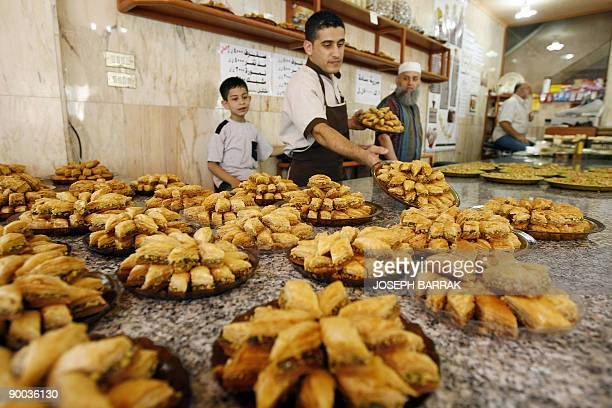 A Lebanese man prepares plates of assorted Baklawa at a confectionary shop in Beirut's Tariq alJadidah neighbourhood on August 24 2009 Muslims all...