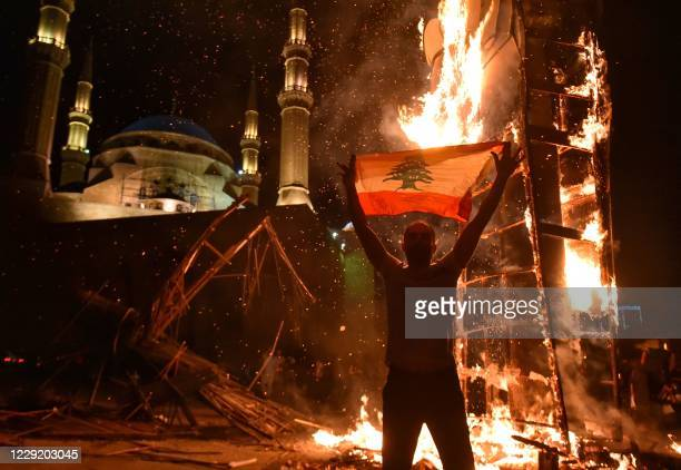 Lebanese man raises a national flag as the Revolution fist, symbol of Lebanons October 2019 uprising, burns after being torched during clashes...