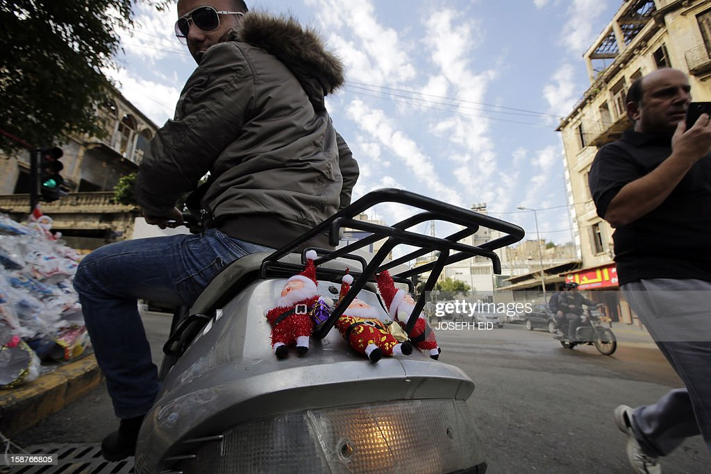 A Lebanese man rides his decorated bike past a street shop displaying ornaments for Christmas and New Year at a street in Beirut on December 28, 2012.