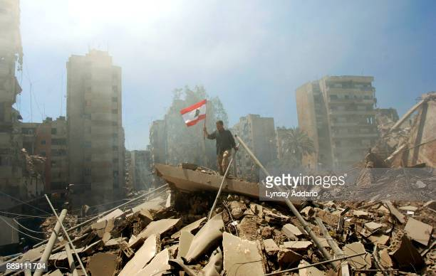 Lebanese man runs across the remains of destroyed buildings carrying a Lebanese flag in an area hit almost daily by Israeli warplanes in Bir al-Abed...