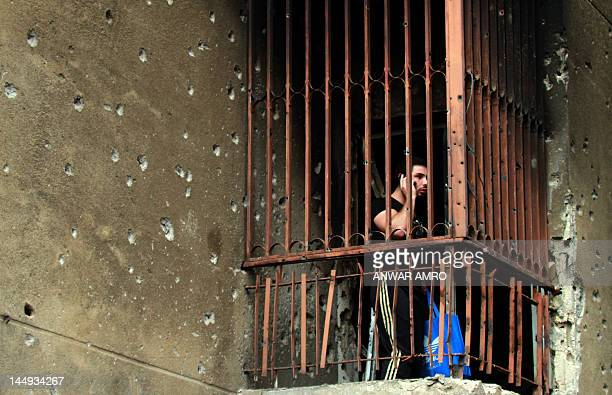 Lebanese man speaks on his mobile phone on the balcony of the offices of the pro-Syrian Arab Movement Party in Beirut on May 21 the morning after...