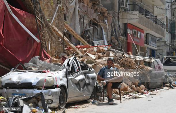 Lebanese man talks on the phone while seated by the rubble of a destroyed traditional building in the Gemmayzeh neighbourhood on August 12 following...