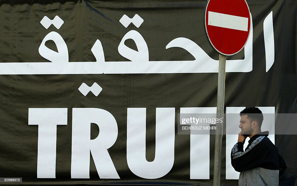A Lebanese man walks past a giant banner reading 'truth' in