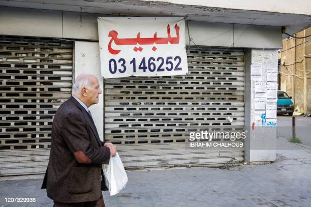 A Lebanese man walks past a store put up for sale in the northern city of Tripoli on February 25 2020