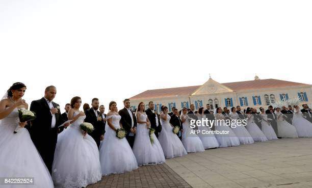 Lebanese Maronite Christian couples take part in a mass wedding at the Maronite Patriarchate in Bkerke on September 3 2017 Twentysix couples got...