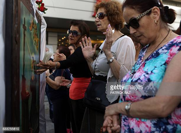 Lebanese Maronite Christian women pray in front of an icon depicting Saint Rita during a procession marking the month of Virgin Mary in the town of...