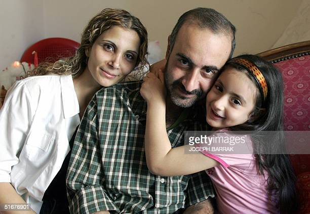 Lebanese Marwan Qassar is hugged by his fiveyearold daughter Marwa and his wife Amal at their home in Beirut 05 November 2004 Qassar was released...