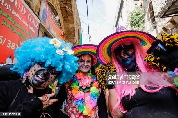 Lebanese men and women dressedup in carnival costumes pose for a picture as they take part in the Zambo carnival held in the northern Lebanese port...