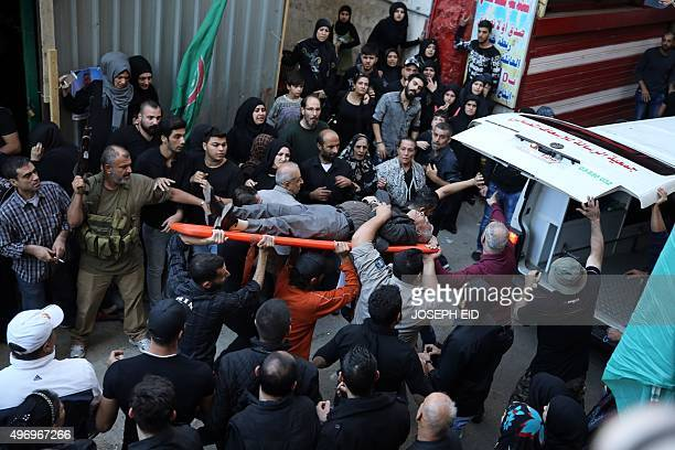 Lebanese men carry a man, who was injured with a ricochet bullet fired during the funeral of Samer Huhu, a man who was killed in a twin bombing...