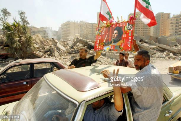 Lebanese men celebrate as they drive through the streets with a poster of Hezbollah leader Sheik Hassan Nasrullah and Lebanese flags in Beirut's...