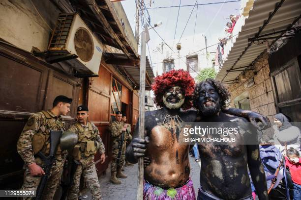 TOPSHOT Lebanese men dressedup in carnival costumes pose for a picture as they take part in the Zambo carnival held in the northern Lebanese port...