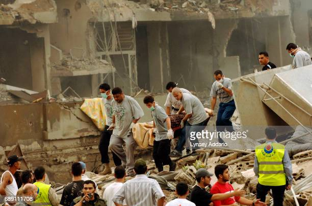 Lebanese men remove a body from the rubble shortly after an attack killing at least 5 people in Beirut's southern suburbs, August 13, 2006. As the...