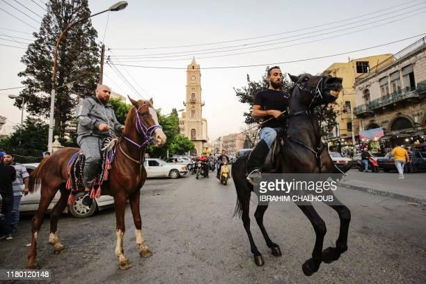 Lebanese men ride horses near the clocktower in the northern port city of Tripoli on November 5 2019