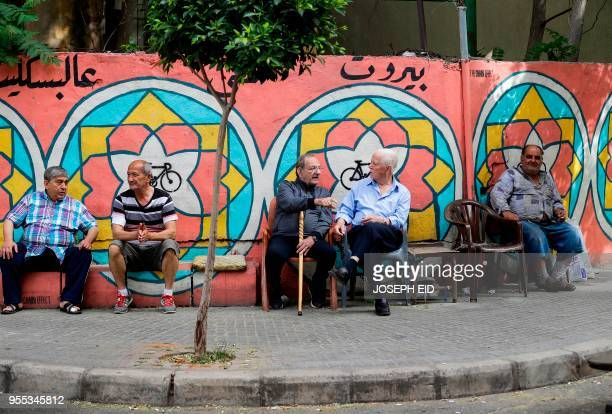 Lebanese men sit on a pavement near the coast in Beirut on May 6 as voters headed to the polls to cast their ballots in the country's first...