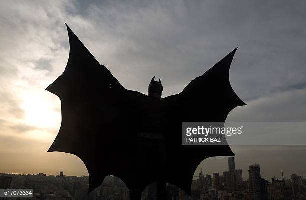 Lebanese model dressed as Batman plays on the rooftop of a building during a photoshoot in the capital Beirut on March 23, 2016. / AFP / PATRICK BAZ