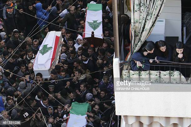 Lebanese mourners carry coffins during the funeral of the victims of two suicide bombings that targeted a cafe the previous day in the Jabal Mohsen...