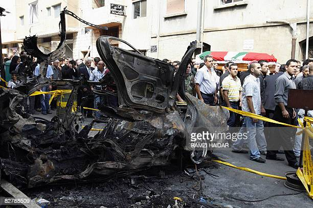 Lebanese mourners carry the coffin of assassinated opposition Druze politician Saleh Aridi past the wreckage of the car in which he was murdered two...