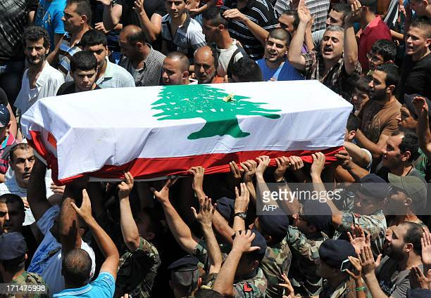 Lebanese mourners carry the coffin of soldier Taleb Hassan Mama during his funeral in the Jabal Mohsen district of the northern city of Tripoli on...