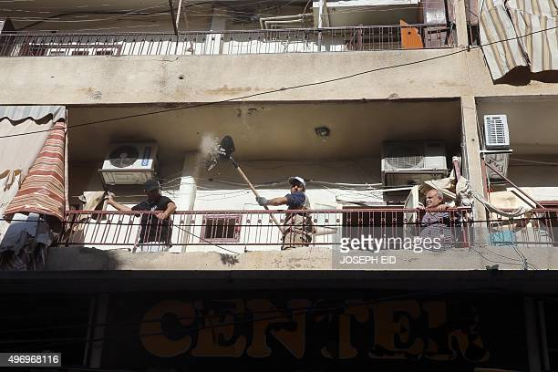 Lebanese municipality workers clear debris from the site of a twin bombing attack in the area of Burj al-Barajneh in Beirut's southern suburb on...