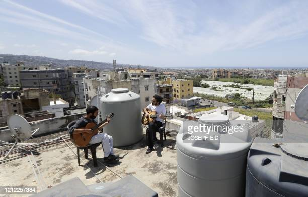 Lebanese Musician Ziad al-Zayyat and his flatmate, interior designer Saad Molaeb, play their guitars on the rooftop of their building, during a...