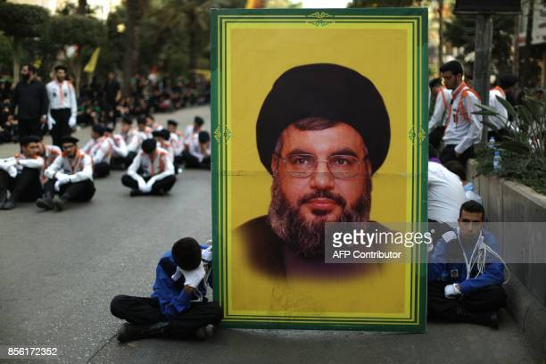 Lebanese Muslim Shiite boy scouts affiliated to Hezbollah pray next to a poster of the movement's secretary general Hassan Nasrallah as they mark...