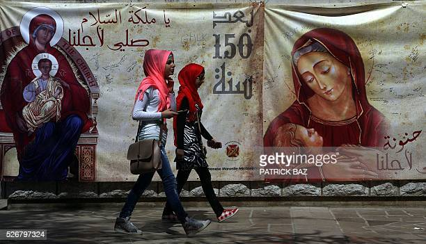 Lebanese Muslim Shiite women walk past a banner depicting Virgin Mary as they pay a visit to the shrine of Our Lady of Lebanon in the town of Harissa...