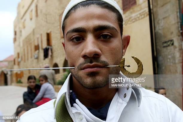 A Lebanese Muslim Sufi young man poses with a spike pierced into his cheek during a ritual ceremony to commemorate the birth of the Prophet Mohammed...