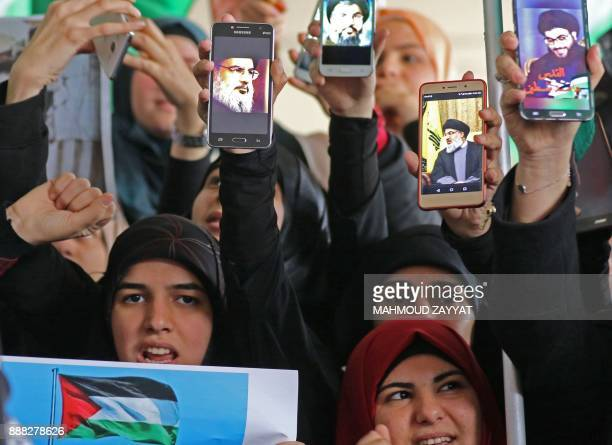 Lebanese Muslim women holding up portraits of the leader of the Shiite movement Hezbollah Hassan Nasrallah on their mobiles and a picture of a...