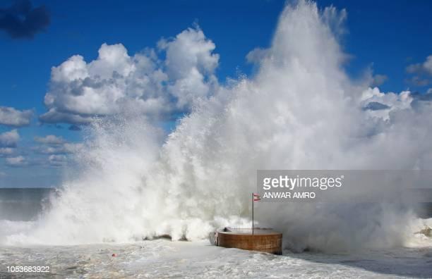 TOPSHOT Lebanese national flag flutters on a dyke as waves crash on the shores of Beirut promenade of alManara on October 26 2018