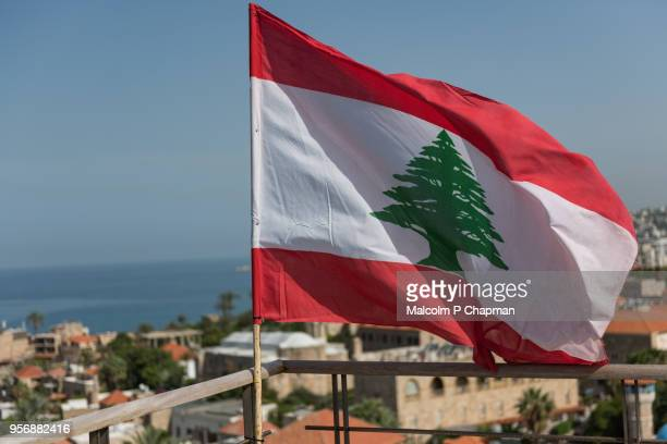 lebanese national flag waving in breeze at byblos, jbeil, lebanon - libanon stock-fotos und bilder