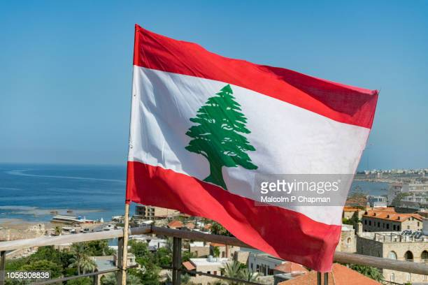 lebanese national flag waving in breeze, byblos, jbeil, lebanon - libanon stock-fotos und bilder