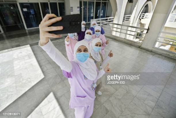 TOPSHOT Lebanese nurses take a selfie as they celebrate International Nurses Day at the Rafik Hariri public hospital in Lebanon's capital Beirut on...