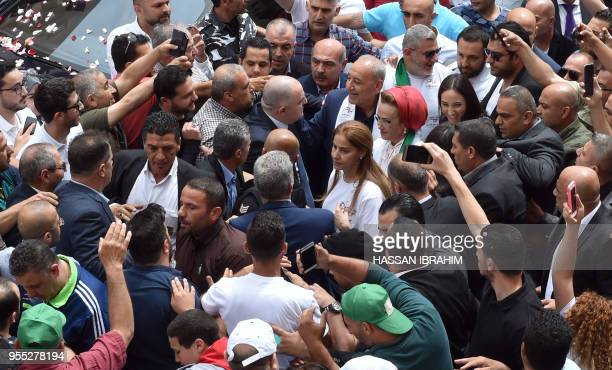Lebanese Parliament Speaker Nabih Berri and his wife Randa are welcomed by supporters as they arrive to cast their votes in the country's first...