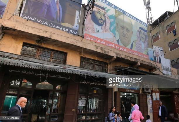 Lebanese pedestrians walk past shops decorated with posters bearing pictures of Saudi Arabia's Crown Prince Mohammed bin Salman his predecessor...