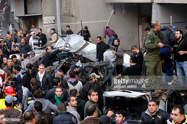 Lebanese people gather at the site of a car bomb that targeted Beirut's southern suburb of Haret Hreik on January 2 2014 At least 20 people were...