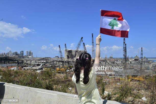 Lebanese people hold Lebanese flag around the site after the deadly explosion at the Port of Beirut led to massive blasts on 4th August in Beirut,...