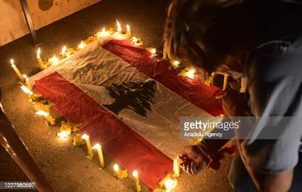 Lebanese people light candles as they gather around the site of explosion to commemorate those who lost their lives after the deadly explosion at the...