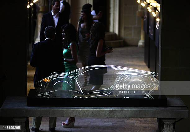 Lebanese people stand behind a Plexiglas model outlining the first WMotors Hyper car as they attend a launch ceremony in Beirut for the premier...