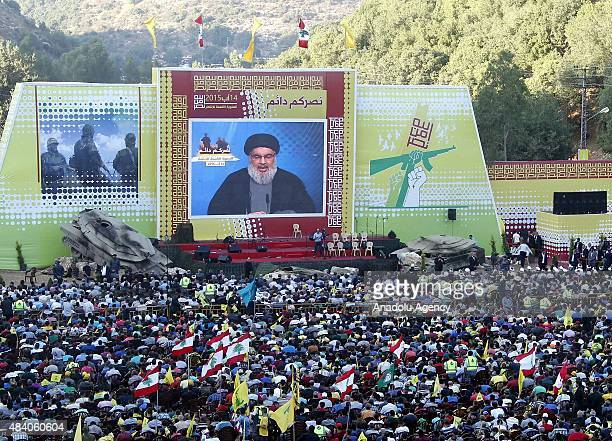 Lebanese people watch on a giant screen Hassan Nasrallah, the head of Lebanon's militant Shiite Muslim movement Hezbollah, giving a televised address...