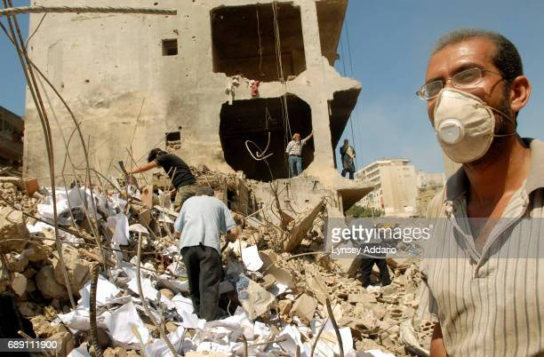 Lebanese pick through the destruction in Beirut's southern suburbs as workers clean up debris and clear roads throughout the neighborhood, August 31,...