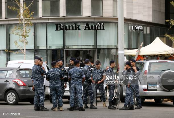 Lebanese police keep watch outside a bank in Beirut on November 1 2019 Lebanon banks reopened for the first time in two weeks today as the country...