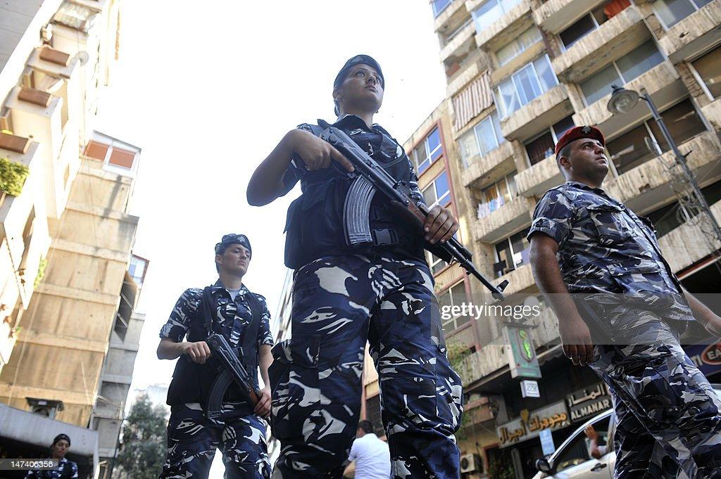 A Lebanese police officer leads female i : News Photo