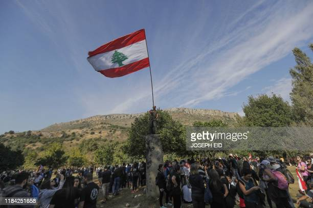 Lebanese portesters raise a national flag as they take part in a 20km march in the Bisri Valley, southwest of the capital Beirut on November 22 to...