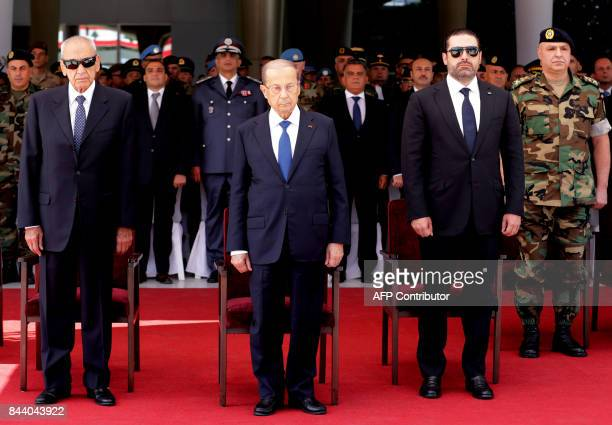 Lebanese President Michel Aoun Prime Minister Saad Hariri and Parliament Speaker Nabih Berri stand to salute 10 fallen Lebanese army soldiers who had...