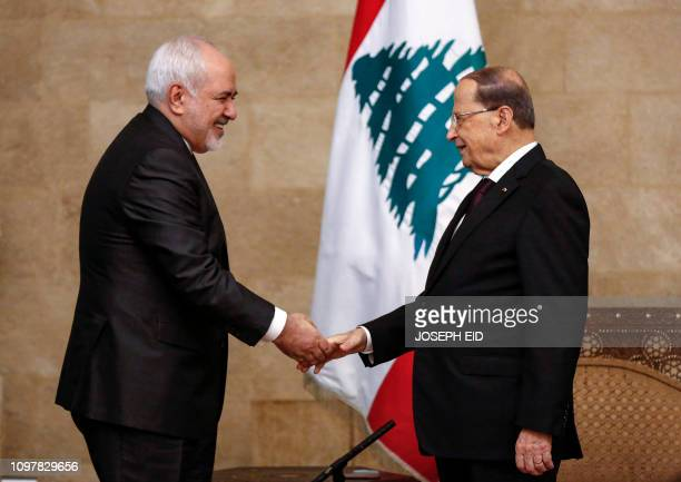 Lebanese President Michel Aoun shakes hands with Iranian Foreign Minister Mohammad Javad Zarif at the presidential palace in Baabda east of the...