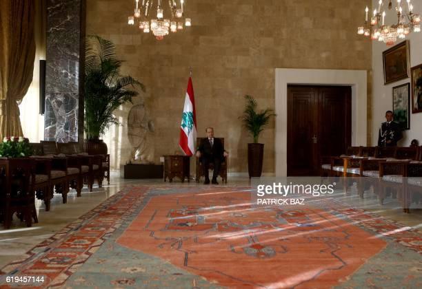 Lebanese presidentelect Michel Aoun sits in the presidential chair at the presidential palace in Baabda east of Beirut on October 31 2016 Lebanese...
