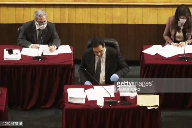 Lebanese Prime Minister Hassan Diab wearing gloves attends a parliament meeting at the Unesco Palace in the capital Beirut, on April 21, 2020. -...
